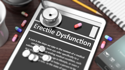 """Tablet with """"Erectile Dysfunction"""" on screen, stethoscope, pills"""